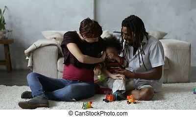 Cheerful diverse family with son relaxing at home
