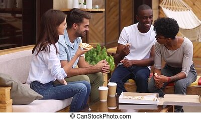 Cheerful diverse friends sitting eating pizza in summer cafe...