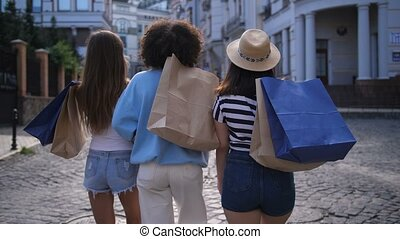 Cheerful diverse friends smiling while shopping