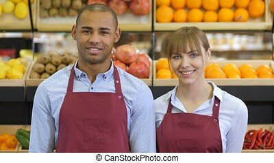 Cheerful diverse shop clerks at grocery store - Portrait of...