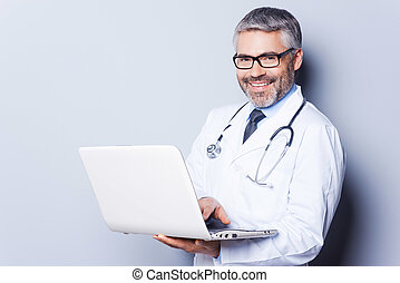 Cheerful doctor with laptop. Confident mature doctor working on laptop while standing against grey background
