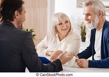 Cheerful elderly couple discussing contract at home