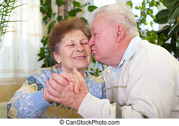 Cheerful elderly couple kissing