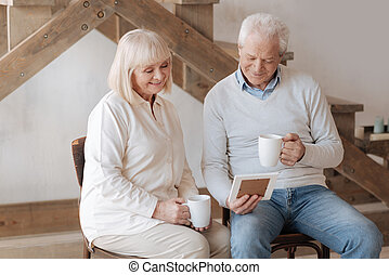Cheerful elderly couple looking at the photo