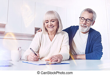 Cheerful elderly couple signing contract