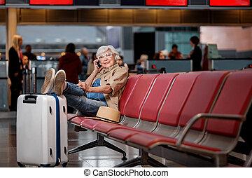 Cheerful elderly lady is calling using smartphone