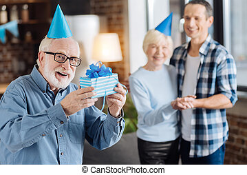 Cheerful elderly man showing present for his son