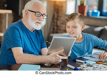 Cheerful elderly man using electronic device