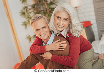 Cheerful elderly married couple resting at home