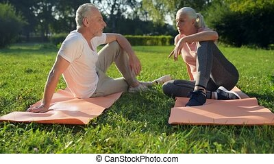 Cheerful elderly sporty couple sitting on the exercise mats...
