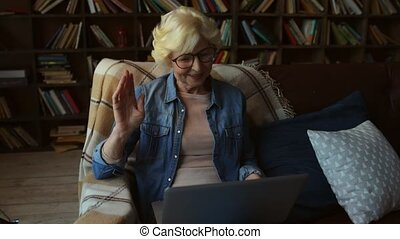Cheerful elderly woman communicating through the Internet -...