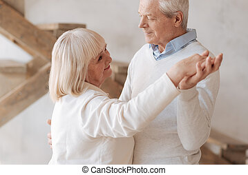 Cheerful elderly woman dancing with her husband