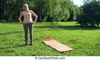 Cheerful elderly woman doing warm up exercises in the park