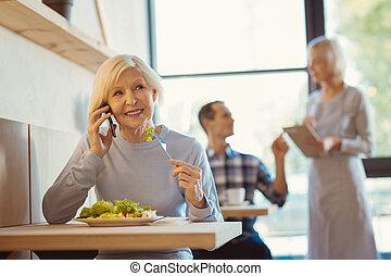 Cheerful elderly woman eating her salad