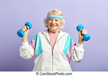 Cheerful elderly woman exercising with a pair of dumbbells and smiling