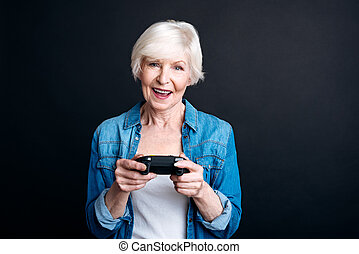 Cheerful elderly woman holdign game console