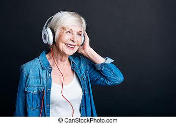 Cheerful elderly woman listening to music