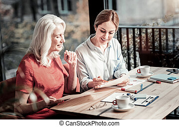 Cheerful elderly woman looking at the drawing of a young experienced designer