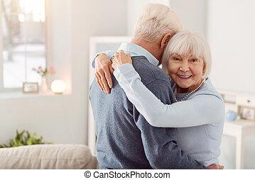 Cheerful elderly woman posing while hugging her husband