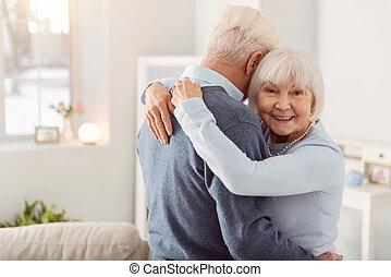 Cheerful elderly woman posing while hugging her husband