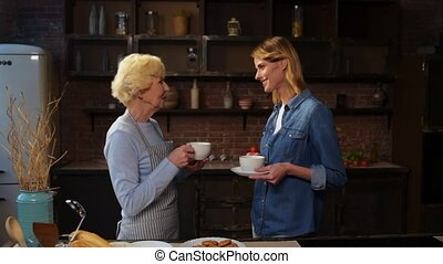 Cheerful elderly woman sharing cookies with her daughter
