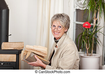 Cheerful Elderly Woman With Firewood