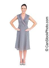 Cheerful elegant brunette in classy dress posing