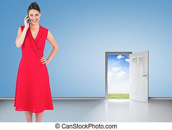 Cheerful elegant brunette in red dress on the phone posing against door opening showing blue sky