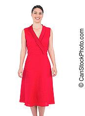 Cheerful elegant brunette in red dress posing