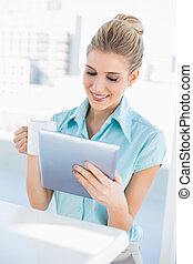 Cheerful elegant woman using tablet holding coffee