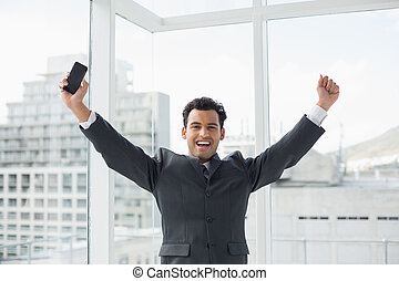 Cheerful elegant young businessman cheering in office -...