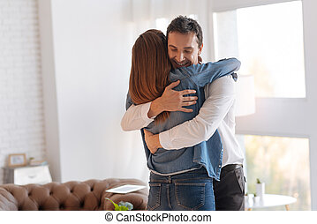 Cheerful emotional man greeting his wife with a promotion at work