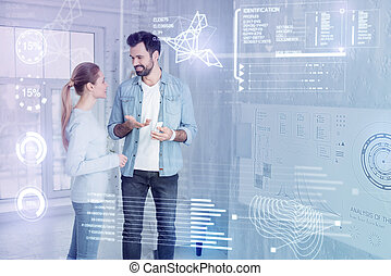 Cheerful engineer smiling while talking to his colleague at home