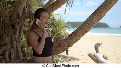 Cheerful ethnic sportswoman talking on smartphone near tree