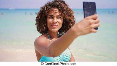 Cheerful ethnic woman taking selfie on beach - Cheerful...