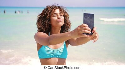 Cheerful ethnic woman taking selfie on beach