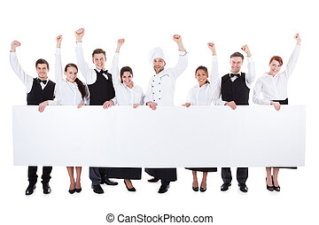 Cheerful excited catering staff showing banner
