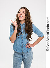 Cheerful excited young woman standing and pointing away