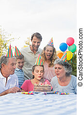 Cheerful extended family blowing out birthday candles together
