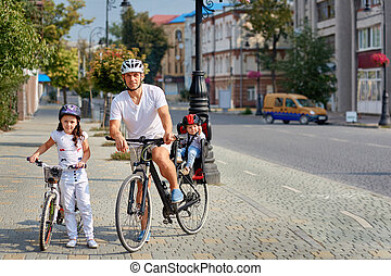 Cheerful family biking in park. Father and two girs ride in...