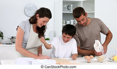 Cheerful family cooking biscuits together in the kitchen