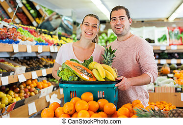 Cheerful family couple standing with full grocery cart after shopping