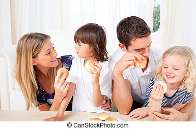 Cheerful family eating burgers in the kitchen