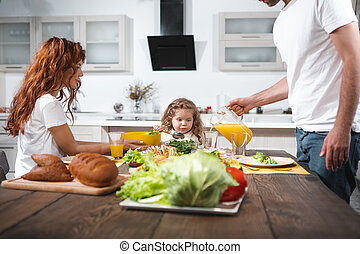 Cheerful family eating in kitchen together
