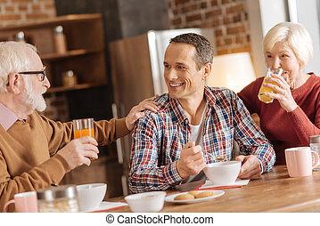 Cheerful family enjoying breakfast in the kitchen