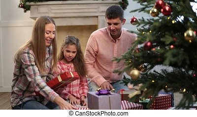 Cheerful family exchanging gifts near xmas tree