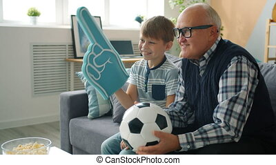 Cheerful family grandfather and grandson watching soccer on TV cheering