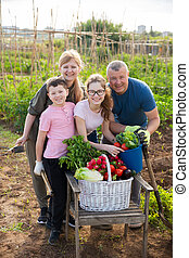 Cheerful family holding vegetables grown in home garden - ...