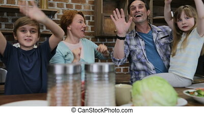Cheerful Family In Kitchen Raising Hands Afrer Cooking Food For Dinner Together Happy Smiling Parents With Two Children