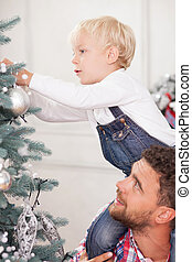 Cheerful family is preparing Christmas tree for celebration